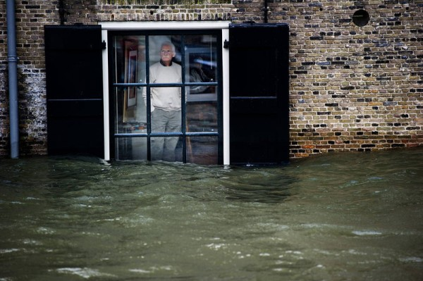 A Dutch local resident, standing in his house, looks to high waters level through his window, in Dordrecht on January 5, 2012. Gale force winds reaching up to 110 kilometres (about 70 miles) an hour as well as heavy rains are expected along the Dutch coast. About a quarter of the country sits below sea level.